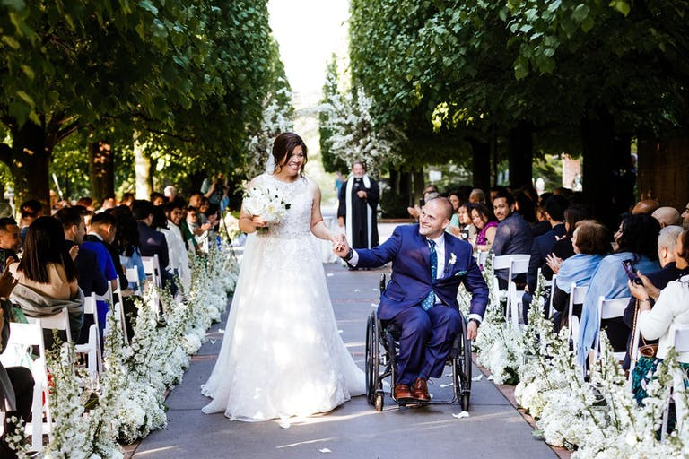 Newlywed couple walking down the aisle surrounded by loved ones at Chicago Botanic Garden, a wedding venue in Chicago Suburbs | PartySlate