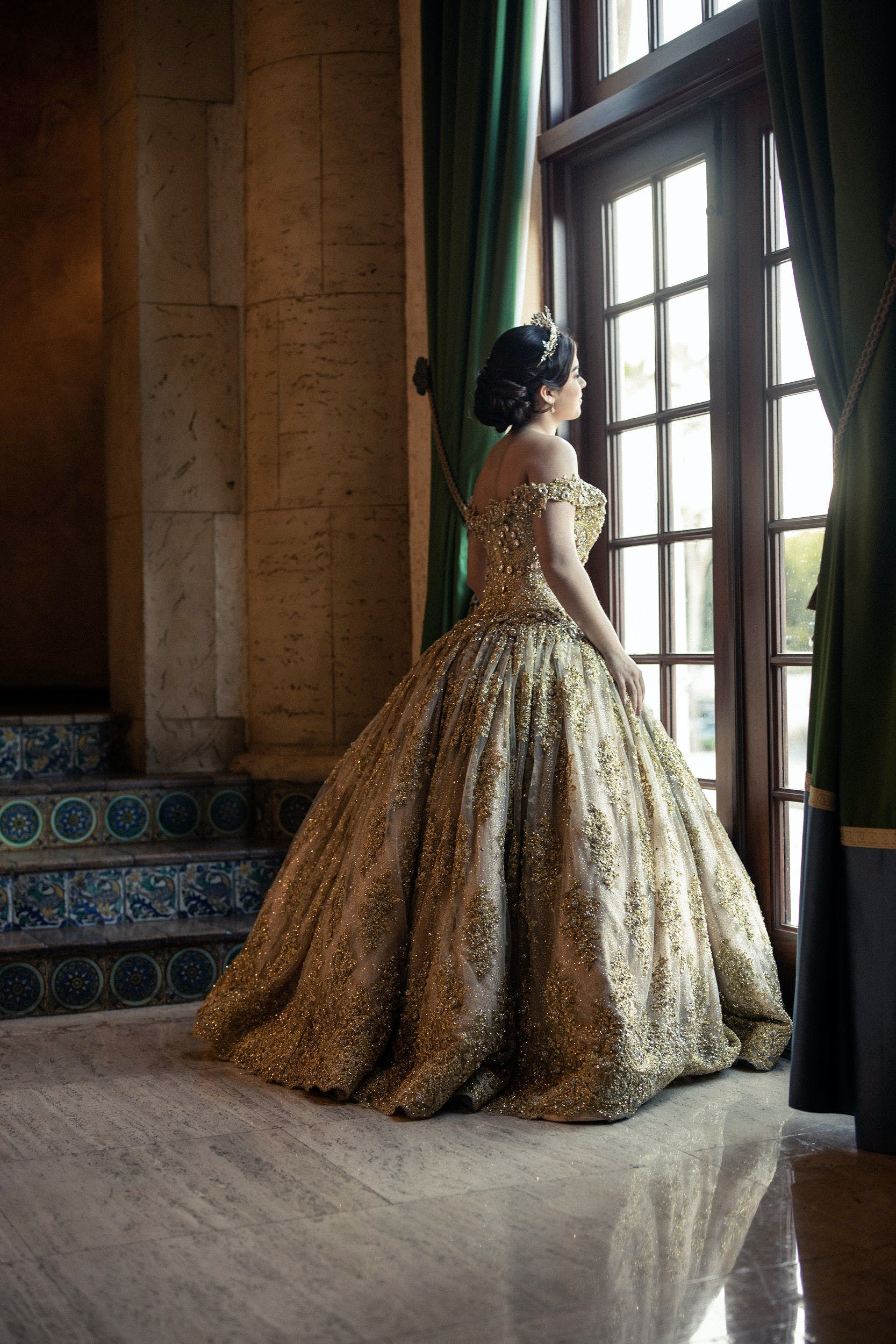 Quinceañera in gold ball gown holds aside velvet drape to look outside floor-to-ceiling window | PartySlate