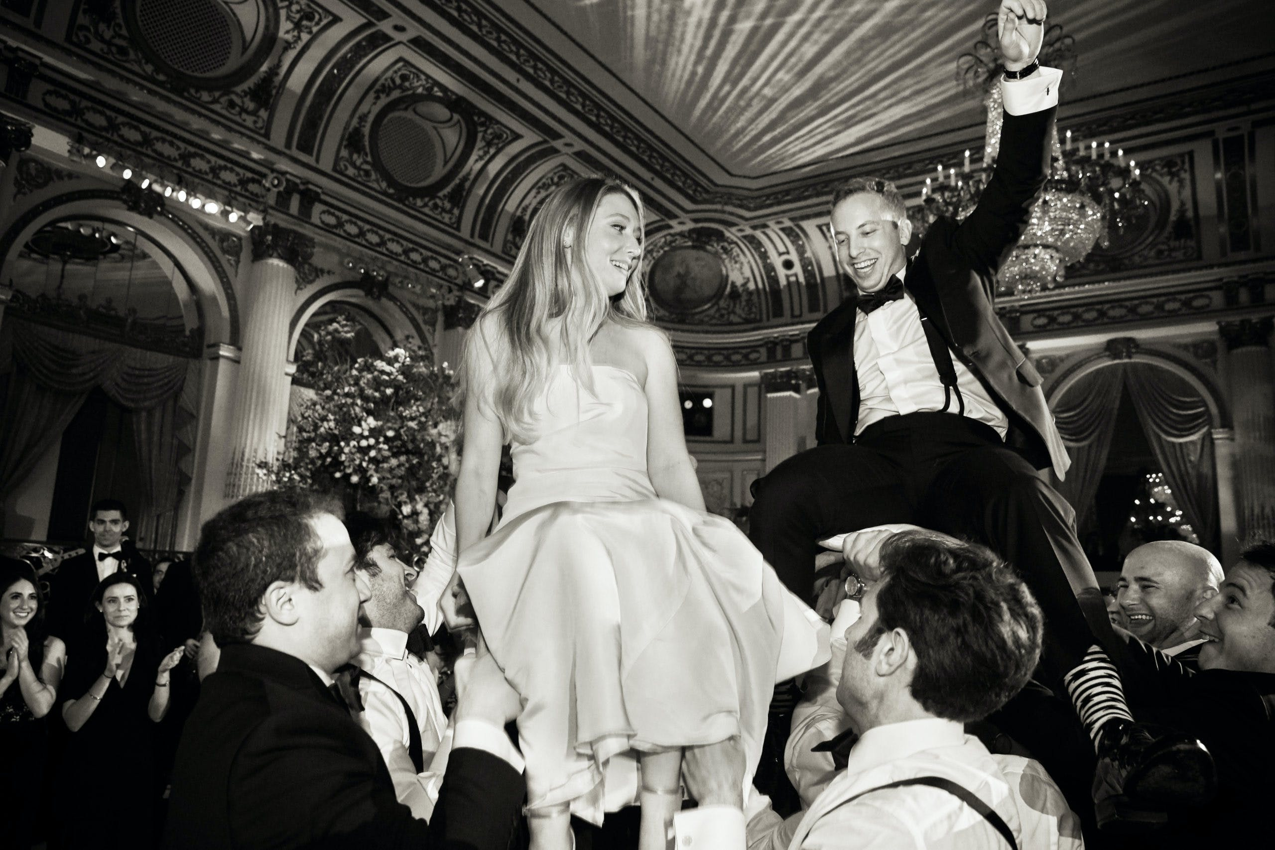 Bride and groom being lifted on chairs on dance floor   PartySlate