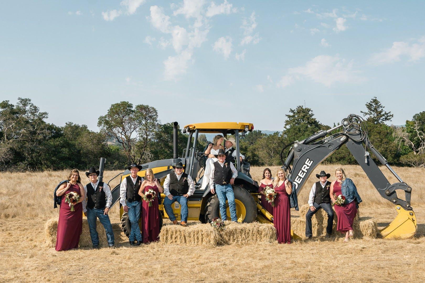 Bridal party in front of tractor machine on farm l PartySlate