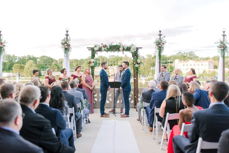 Two grooms sharing vows at a peaceful countryside ceremony at Hotel Baker in St. Charles, IL | PartySlate