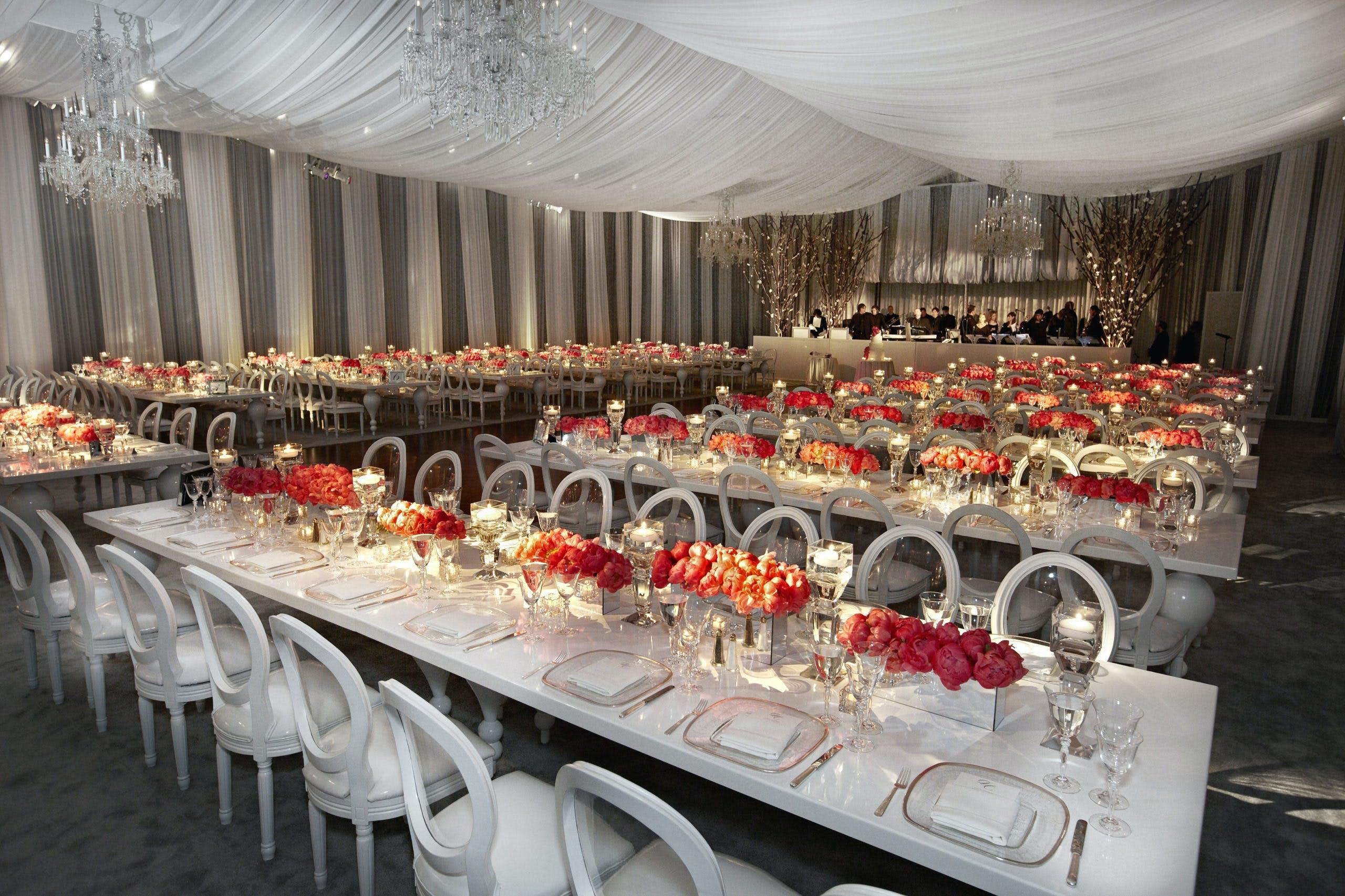 Tented reception venue with orange floral centerpieces l PartySlate