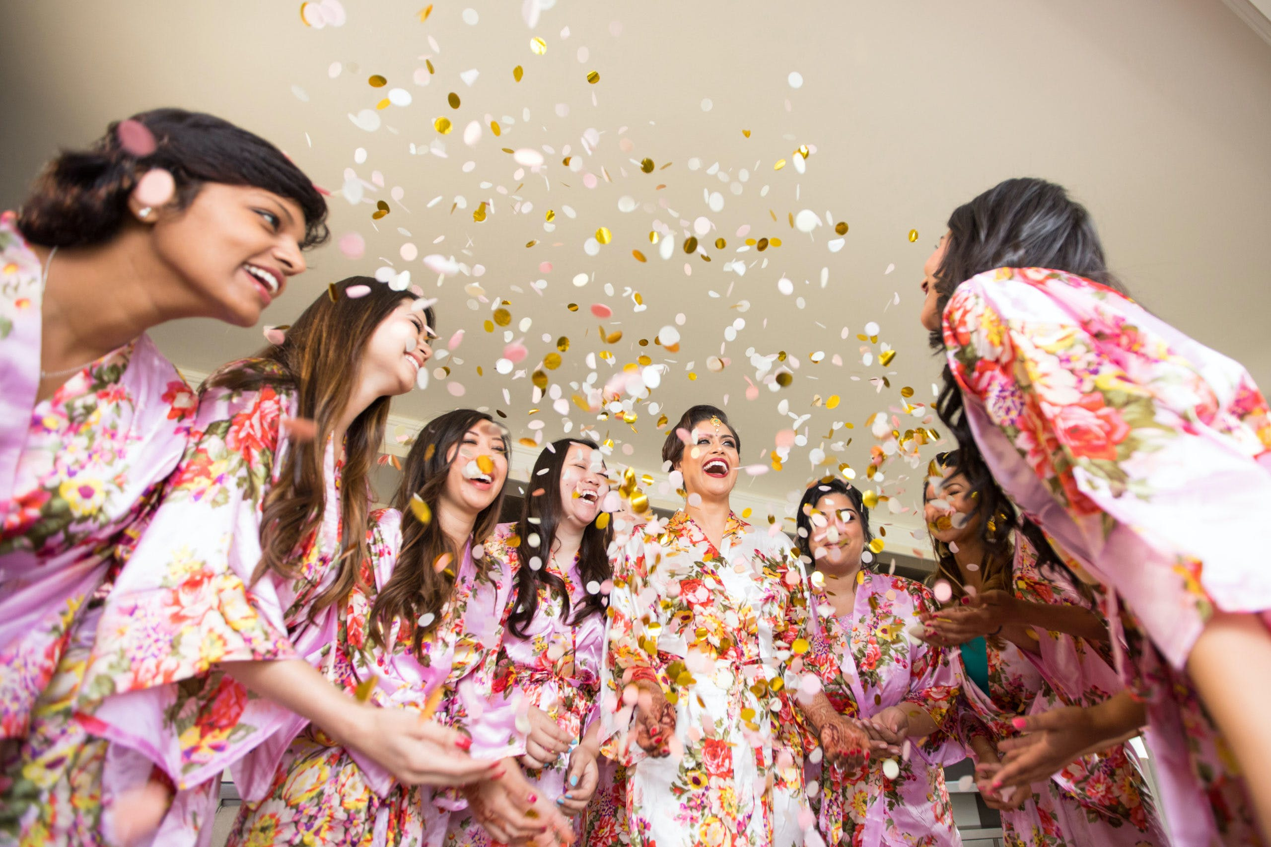Bridesmaids huddled around in matching pajamas and confetti thrown in air   PartySlate