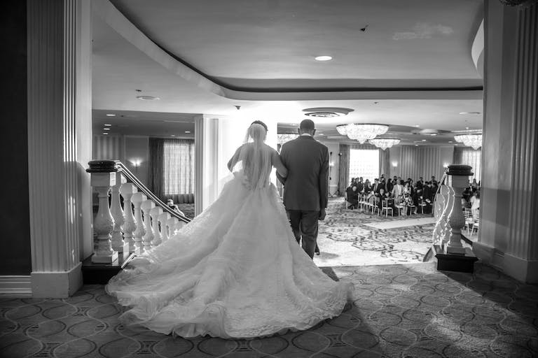 Bride and groom descend iconic stairway to Grand Ballroom at Hilton Orrington Hotel Evanston | PartySlate