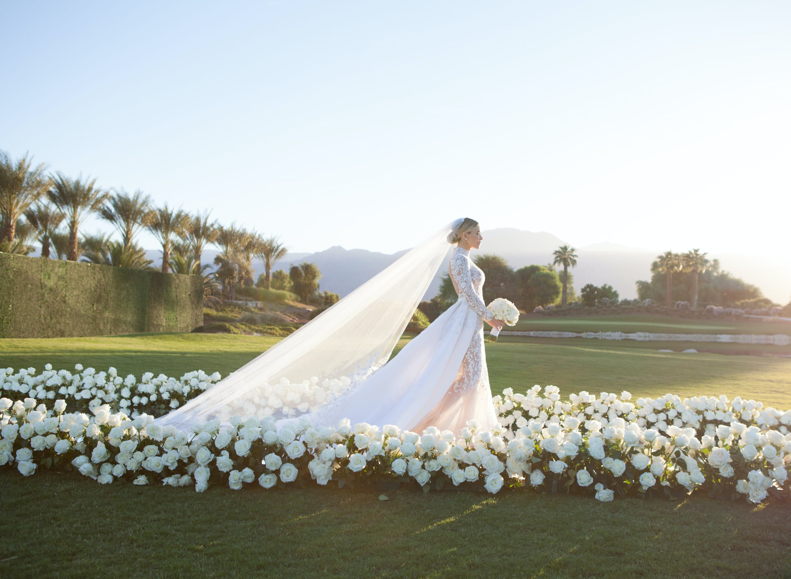 Side profile shot of bride walking down aisle surrounded in white florals and greenery backdrop   PartySlate