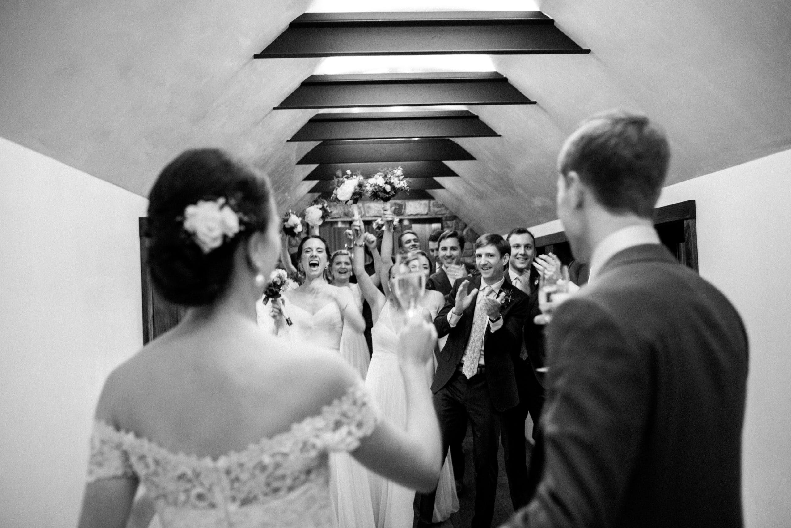 Black and white photo or bride and groom looking at cheering bridal party l PartySlate