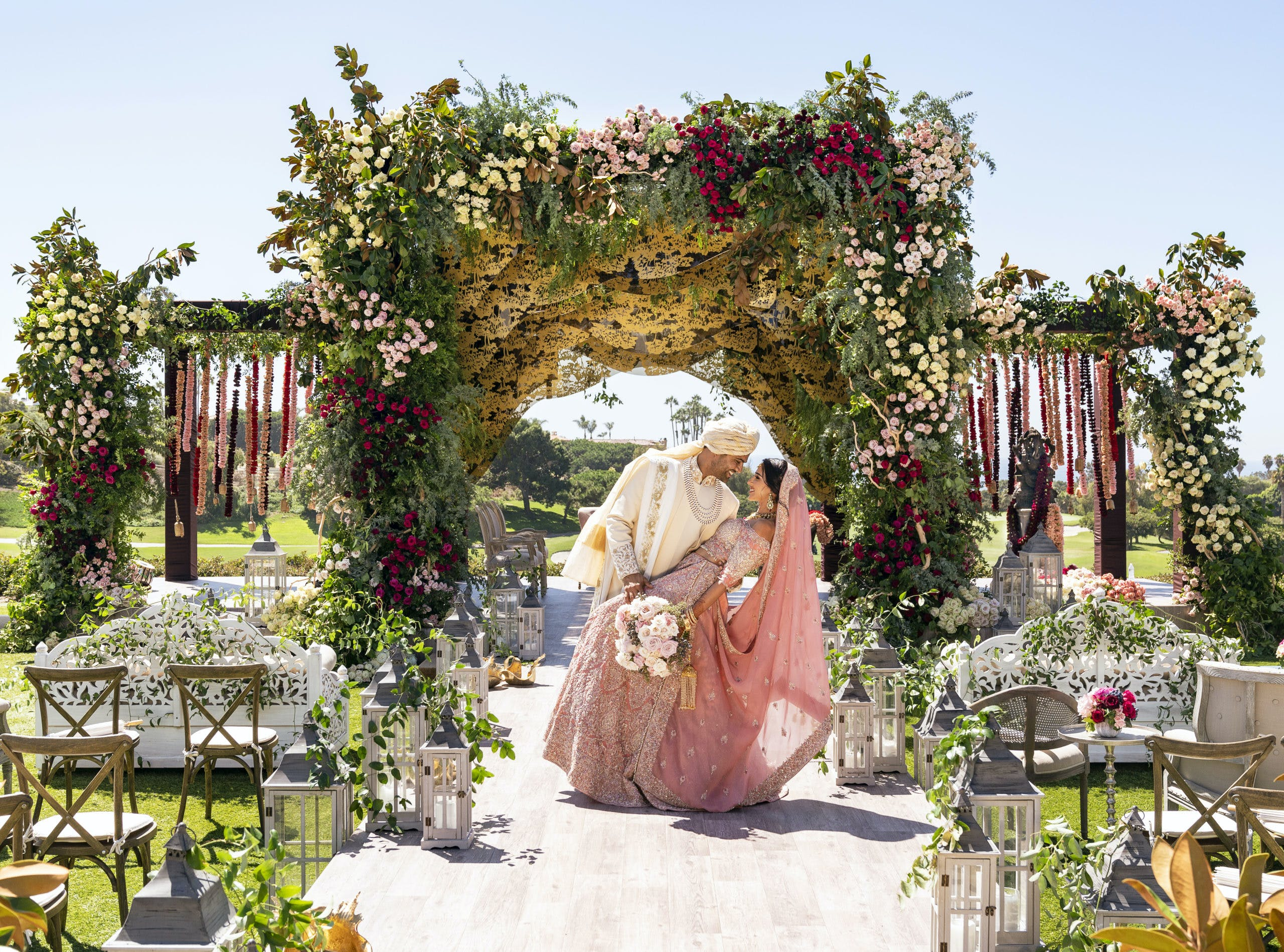 Groom dipping bride at traditional Indian wedding with colorful florals and greenery backdrop   PartySlate