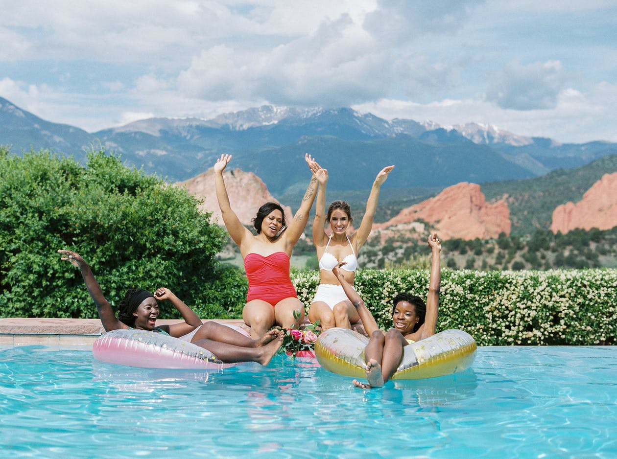 Four Friends Pose in Pool With Floaties Against Mountain Backdrop for Best Bachelorette Party Destinations   PartySlate