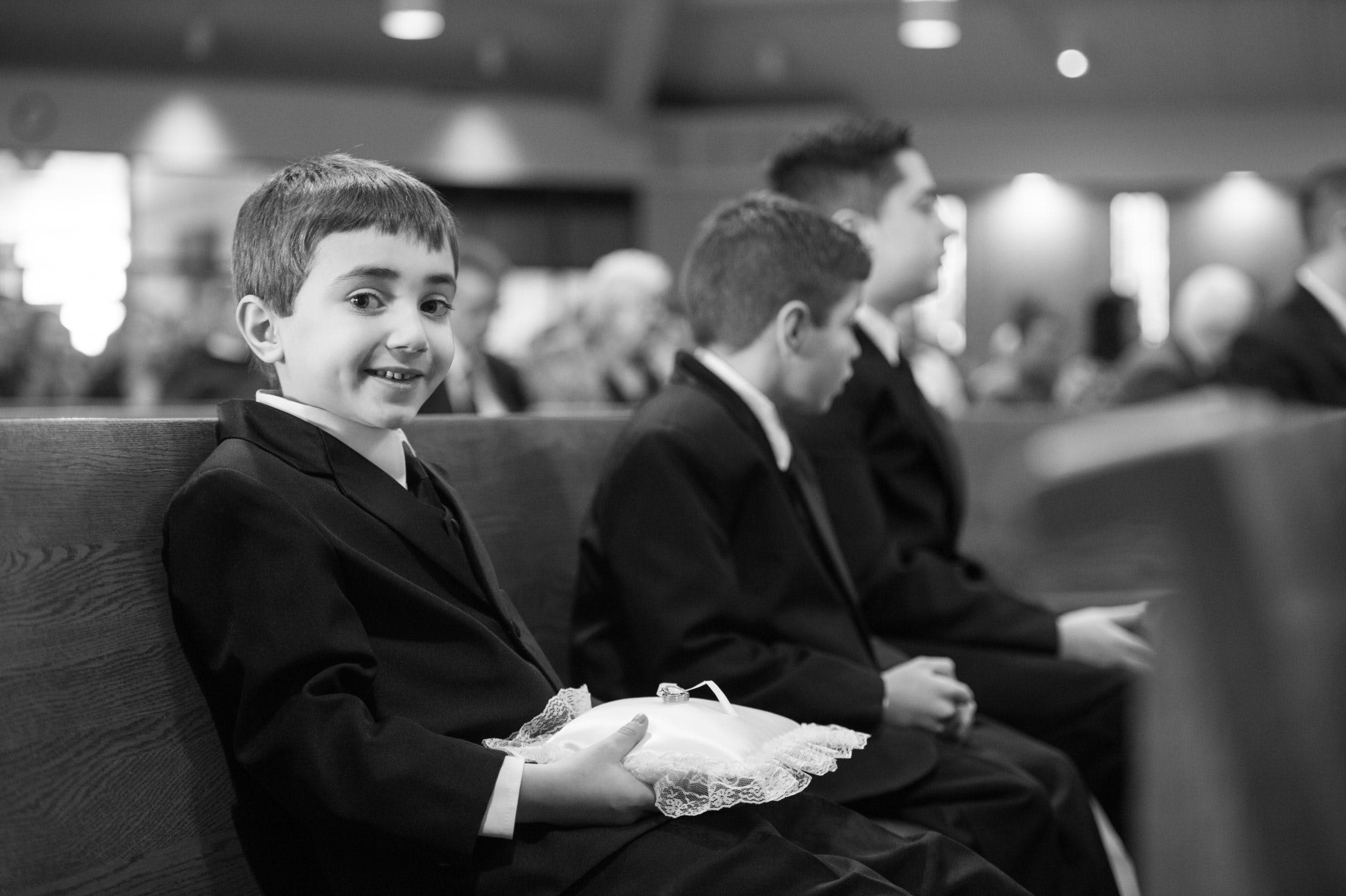 Black and white photo of two young boys sitting in church pue l PartySlate