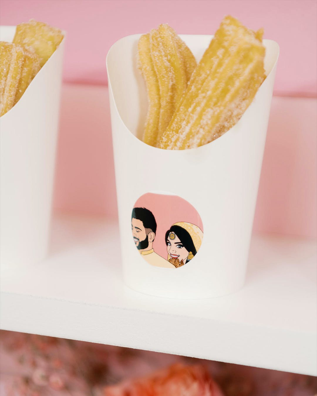 Churros in white packaging with cartoon version of engaged couple's face for engagement party | PartySlate
