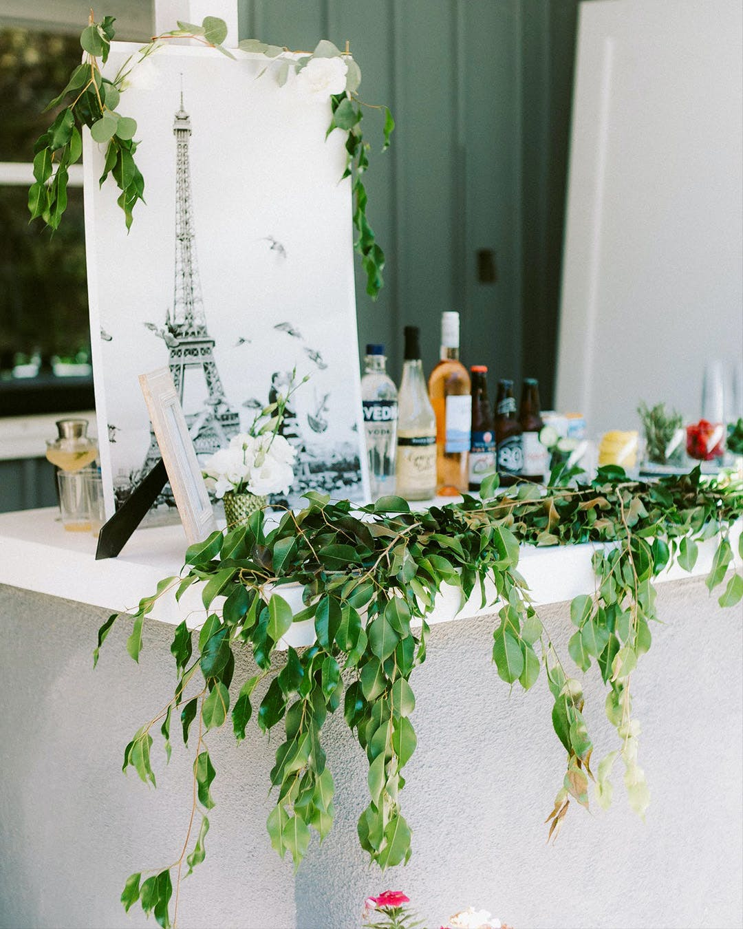 Bar set up with greenery and Signage of the Eiffel Tower for Paris-themed engagement party | PartySlate