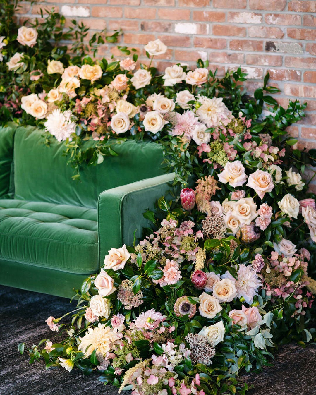 Green velvet sofa with cascading roses for engagement party in the spring | PartySlate