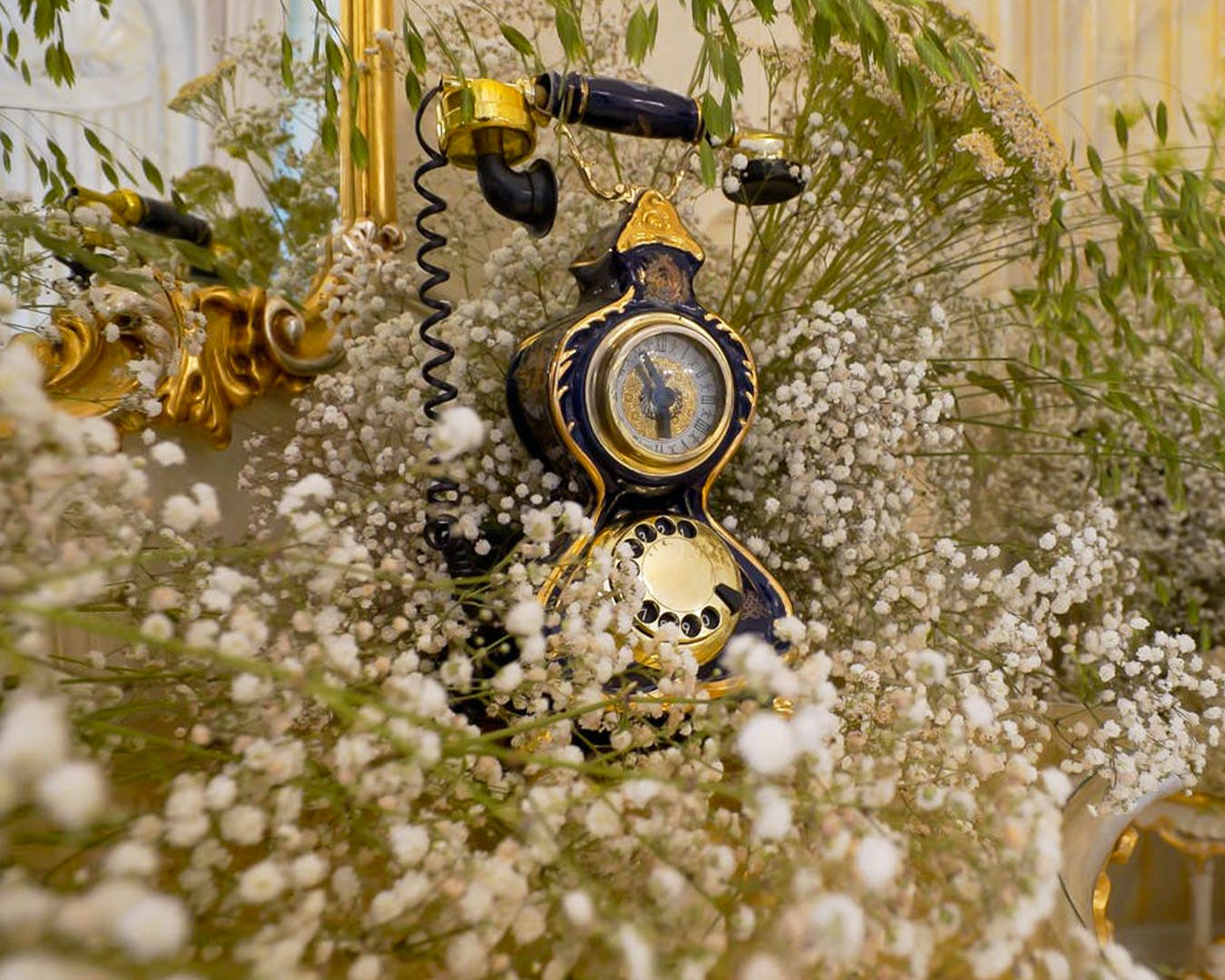 Vintage telephone covered in baby's breath for London-themed engagement party idea | PartySlate