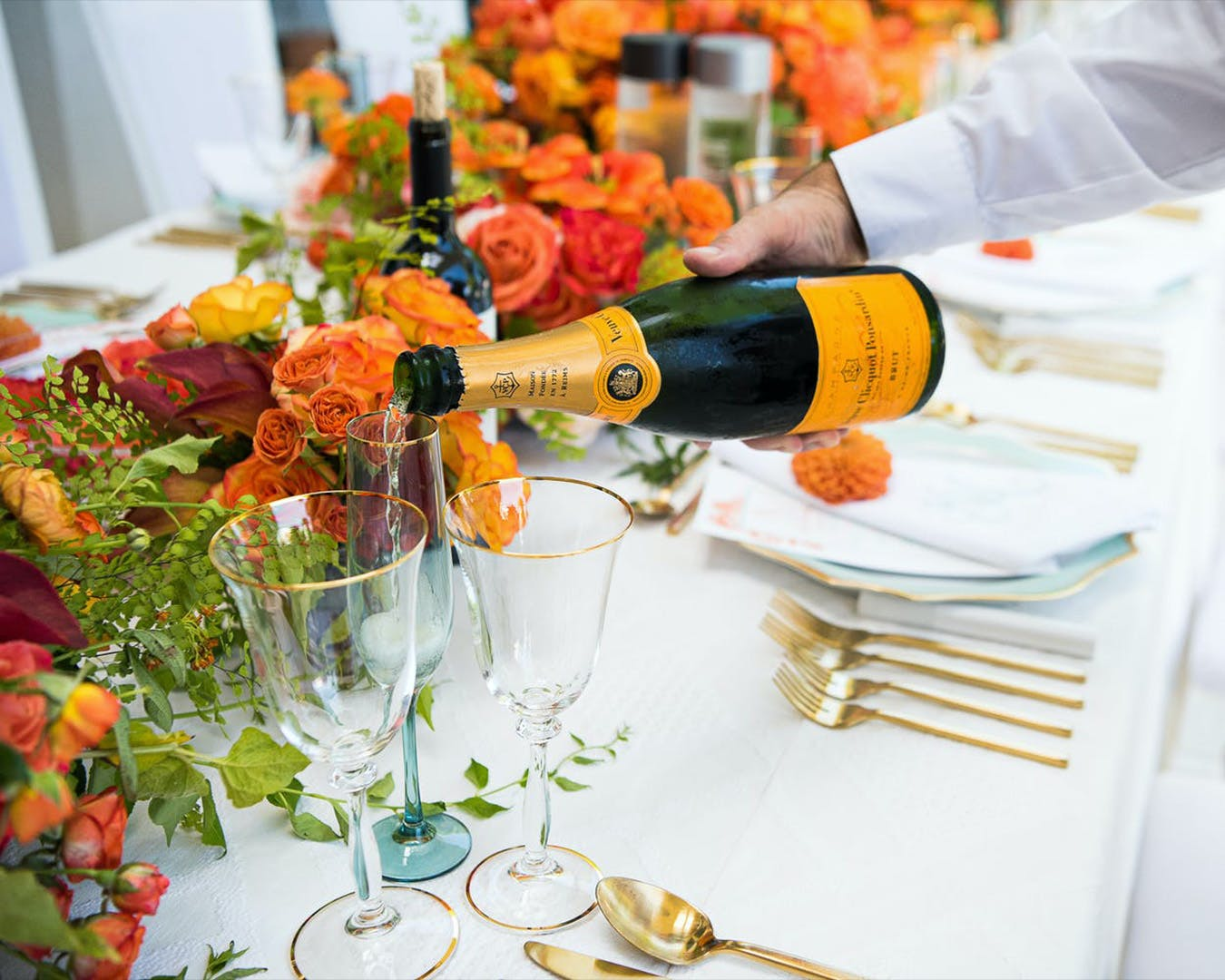 Server pours Champage at table laden with orange flowers and greenery for engagement party | PartySlate