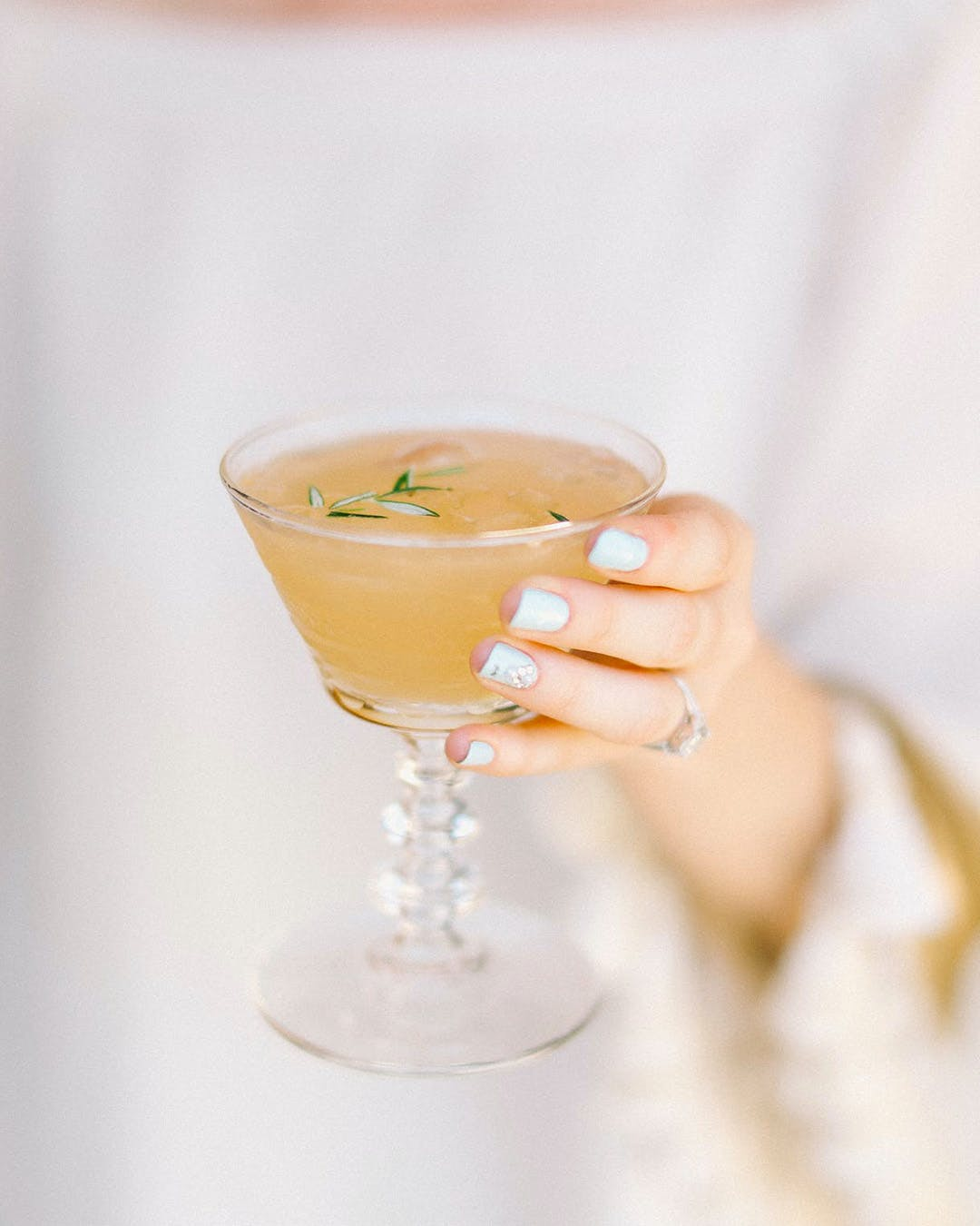 Manicured hand holds custom cocktail at engagement party | PartySlate