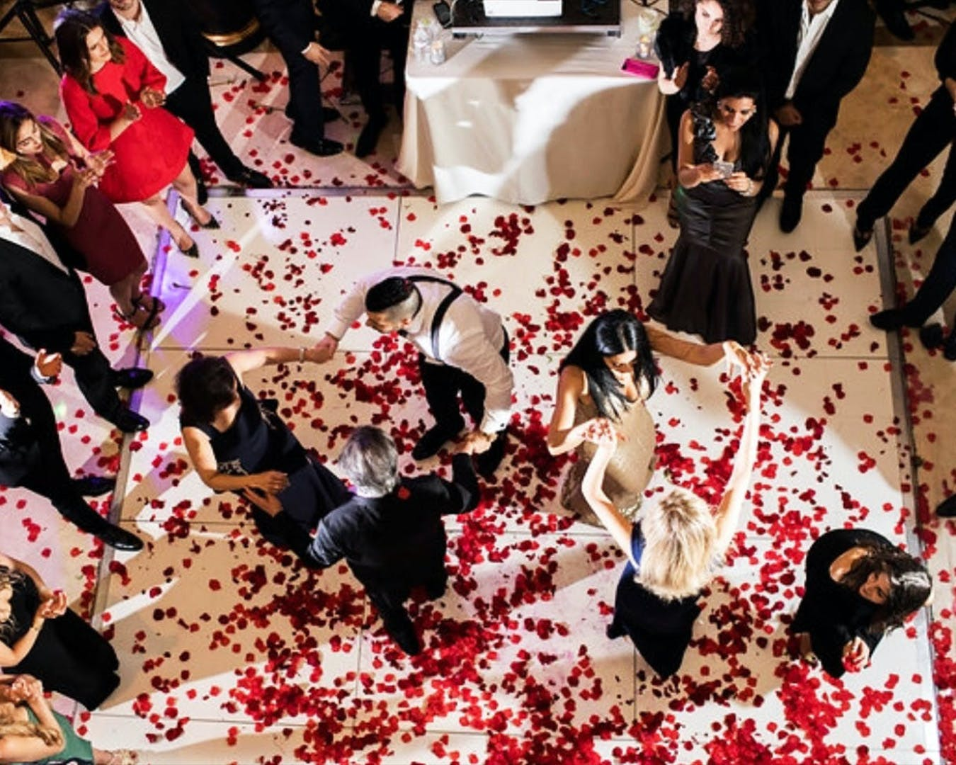 Guests dance on a white dance floor covered in red rose petals at engagement party | PartySlate