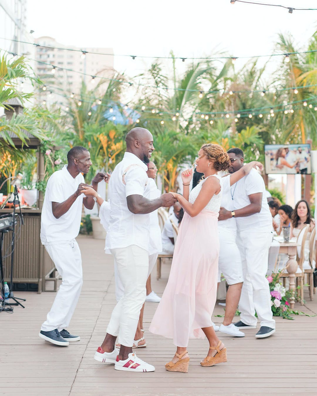 Guests dance at outdoor engagement party with greenery | PartySlate