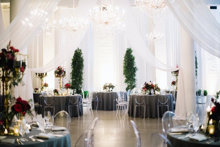 all-white sheer drapery framing wedding aisle flanked by topiaries at Chez in Chicago   PartySlate