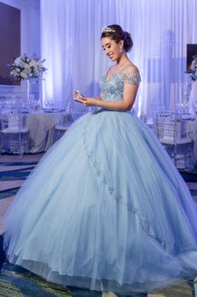 Quinceañera in Blue Cinderella Ballo Gown Stares at Glass Slipper in Purple-Uplit Ballroom Reception Planned by The Soirée Co. Wedding and Event Planning | PartySlate