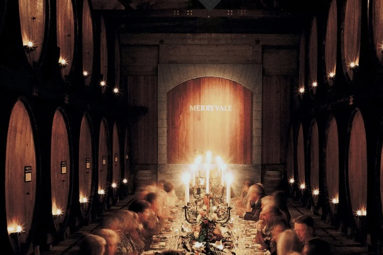 Merryvale Vineyards' Historic Cask Room hosting a candle-lit dinner with guests engaged in conversation  PartySlate