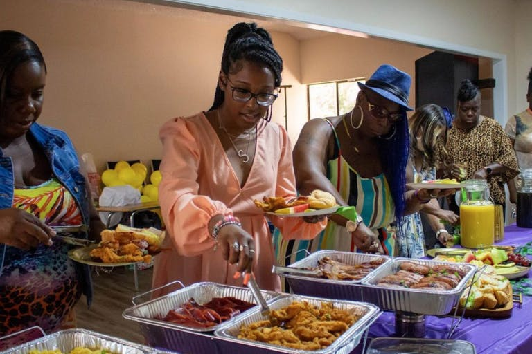 Women serve themselves from buffet of Mama Tecia's Catering   PartySlate
