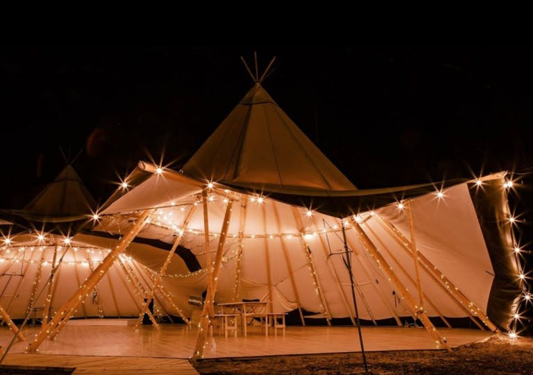 Nighttime wedding reception in Nordic tipi at At the Shire in Piney Woods   PartySlate
