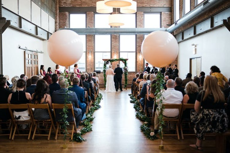 high ceiling Art Deco space with greenery lined wedding aisle with two giant white balloons   PartySlate