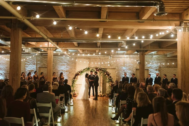 candle-lined wedding aisle and string lights lead to floral arch in Chicago   PartySlate