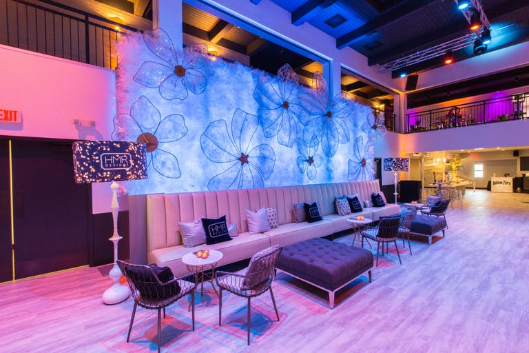 pink and purple lit raw space with towering open ceiling and second floor overlook for wedding in Chicago   PartySlate