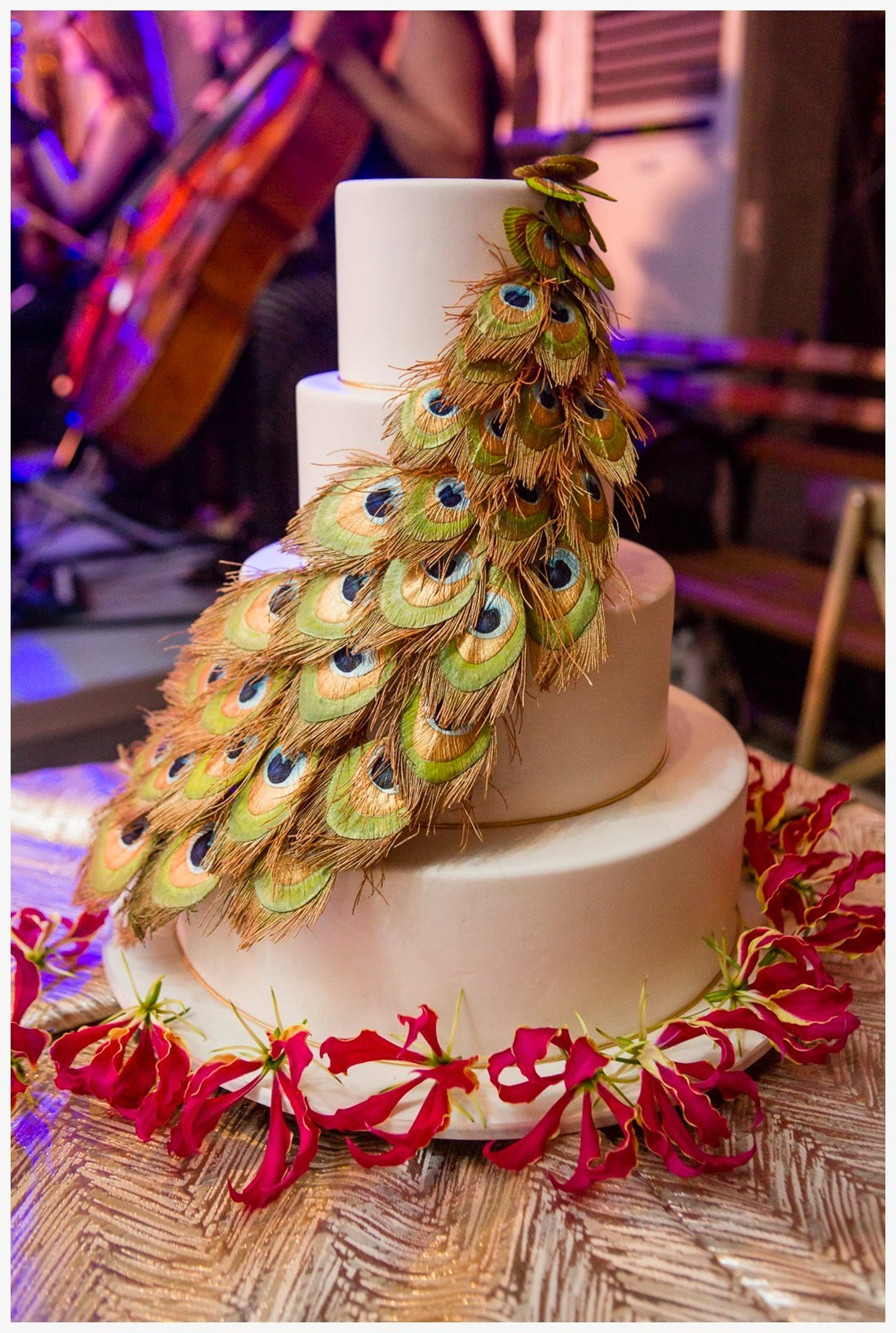 Three-tier white wedding cake with cascading peacock feathers | PartySlate