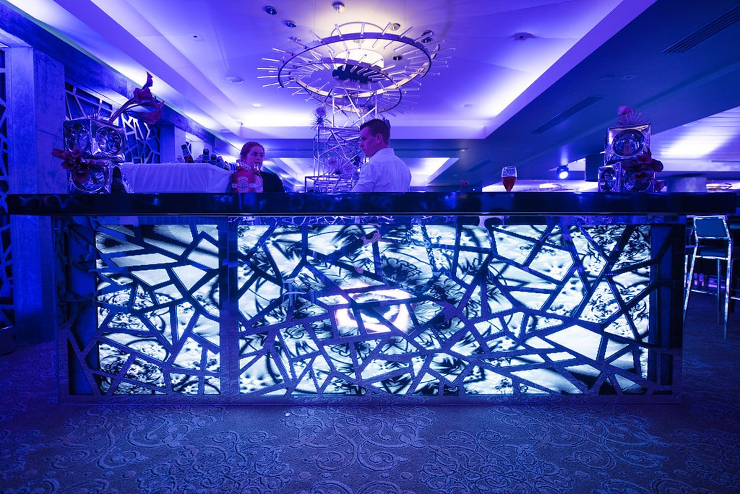 50th-birthday party with uplit ice-blue bar with geometric and fractured paneling in purple-uplit ballroom | PartySlate