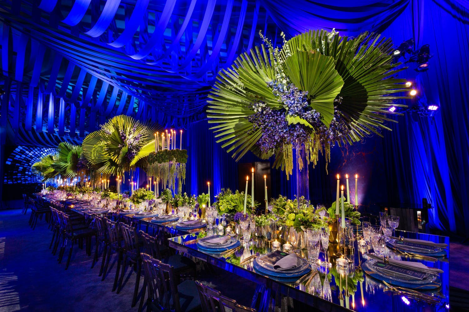 Blue lapis-inspired anniversary party with bright blue ceiling décor and greenery centerpieces | PartySlate