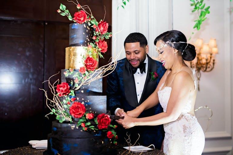 Bride and Groom Cut Into Glamorous Rose-Decorated Black and Gold Cake at Wedding Planned by The Savvy Consultants of Houston, TX   PartySlate