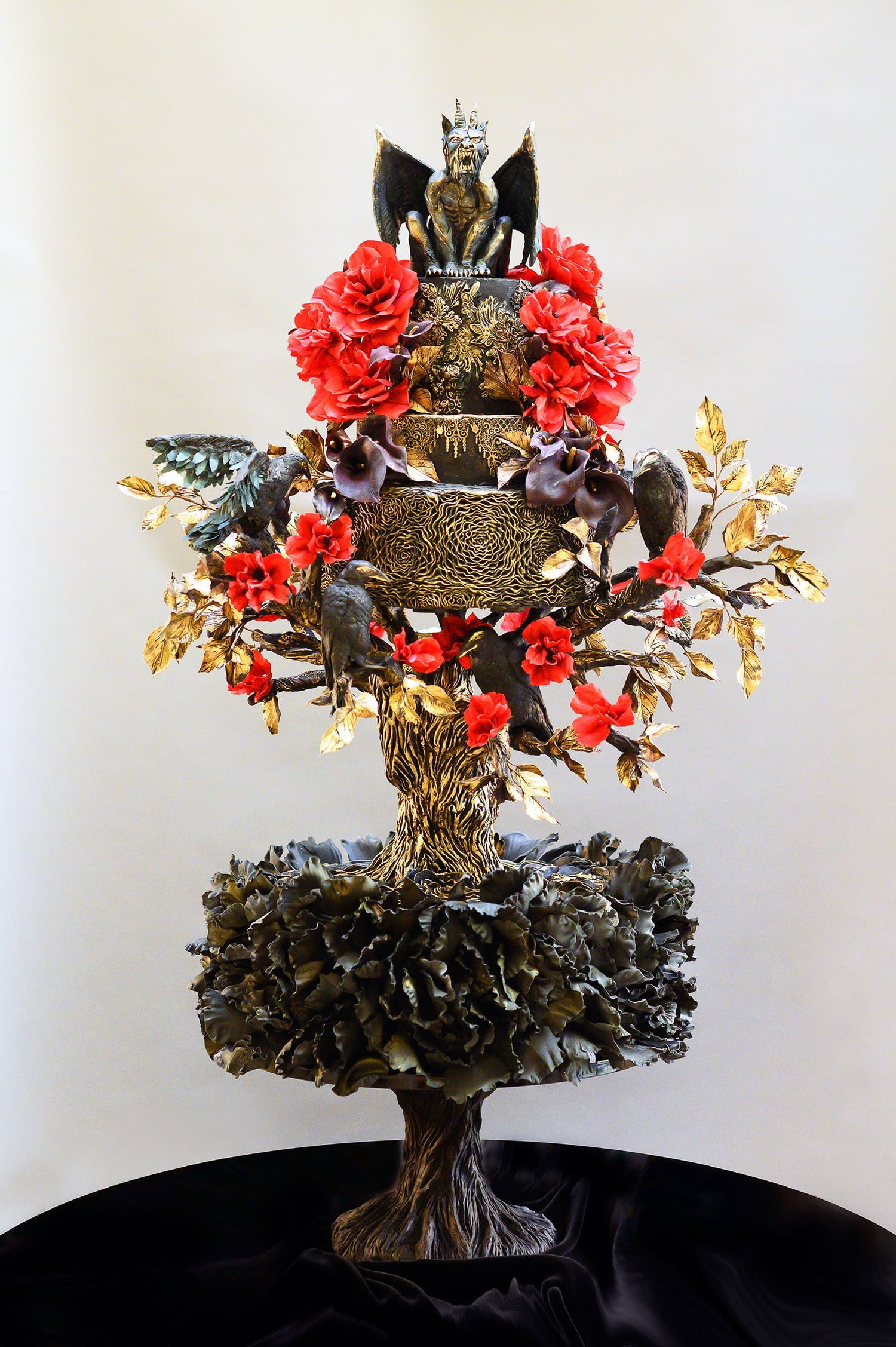 Unique black goth wedding cake with gargoyle topping and red and gold blooms | PartySlate