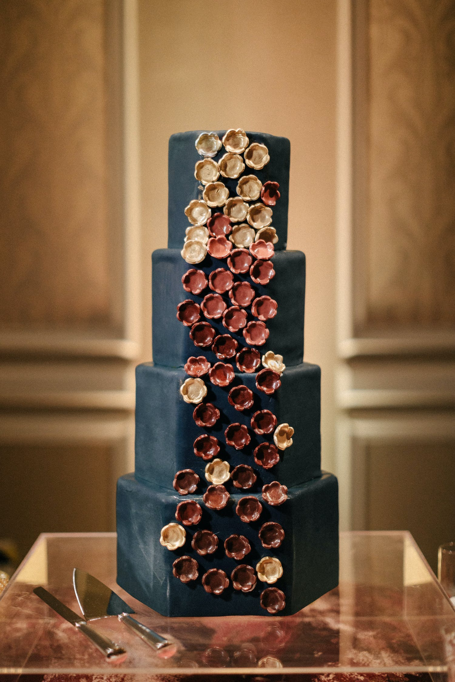 Four-tier black wedding cake with burnt-red, pink, and gold candied flower designs down side | PartySlate