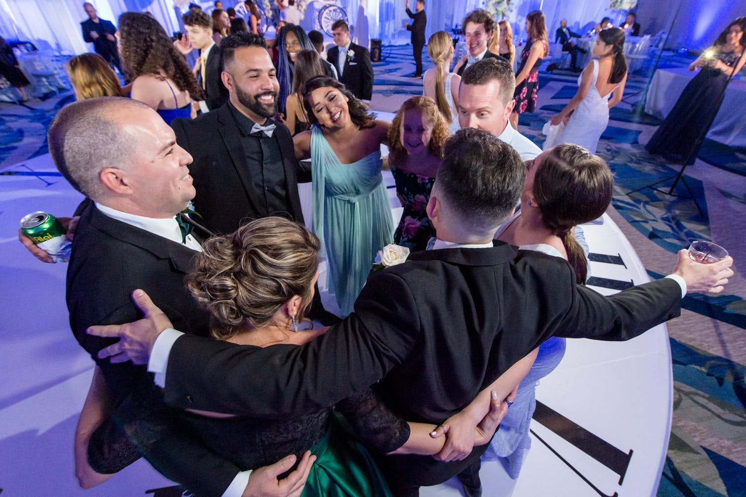 Friends and family hug on dance floor at quinceañera | PartySlate