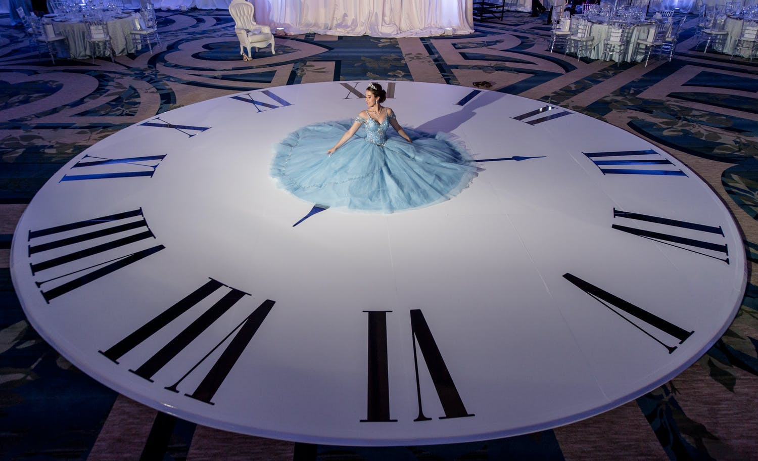 Quinceañera sits in blue ball gown on clock-shaped dance floor | PartySlate