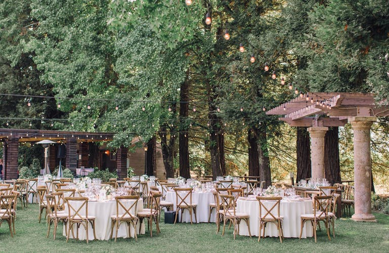 Outdoor reception area with white tables and wooden chairs encircled by vibrant trees decorated with dangling lights at Trentadue Winery in Geyserville, CA   PartySlate