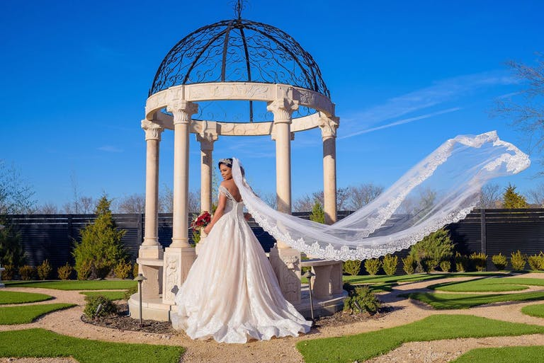 Bride with blowing veil stands in front of pillared wedding arch with filigree dome   PartySlate