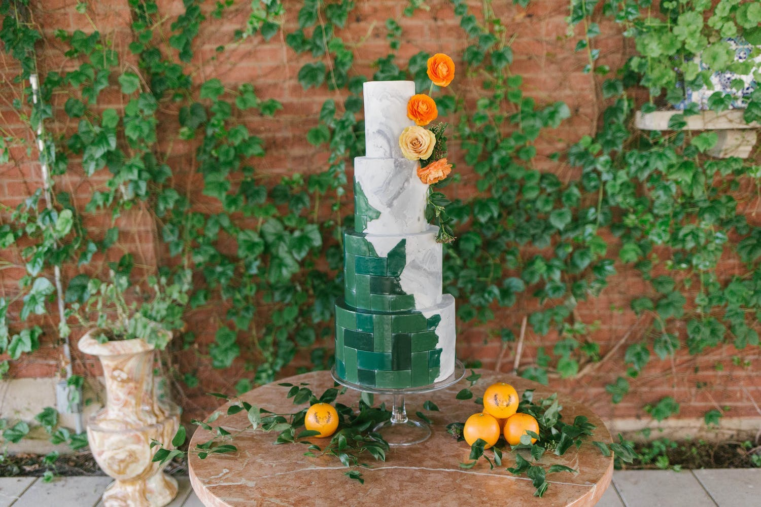 Four-tier circular wedding cake with mix of green tile designs and grey marble | PartySlate