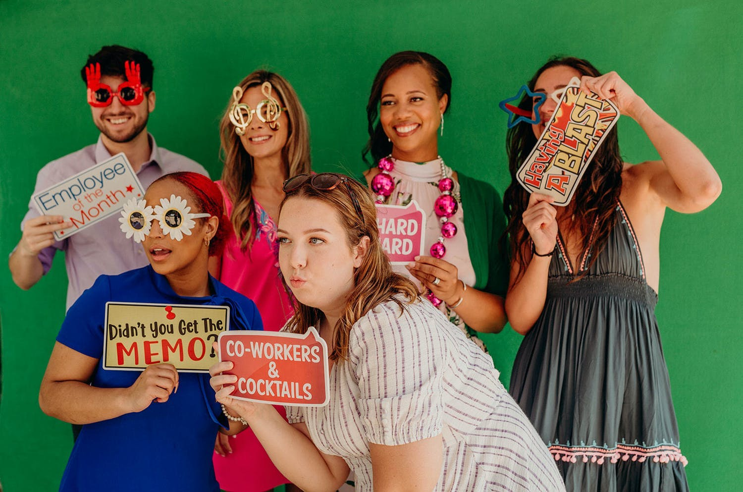 Guests pose against green backdrop at corporate event with fun photo props | PartySlate
