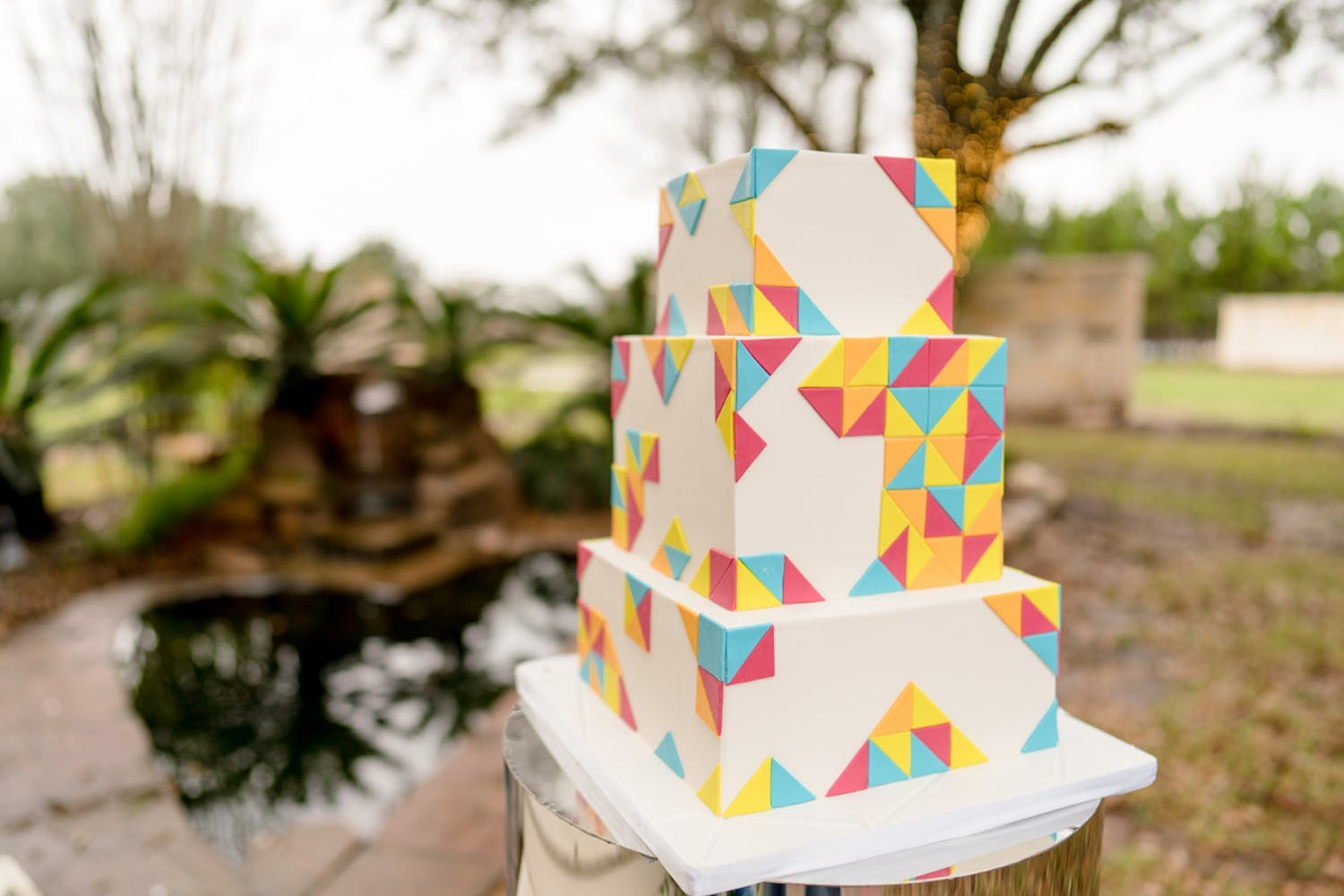 Three tier square wedding cake with multi-color tangram designs | PartySlate