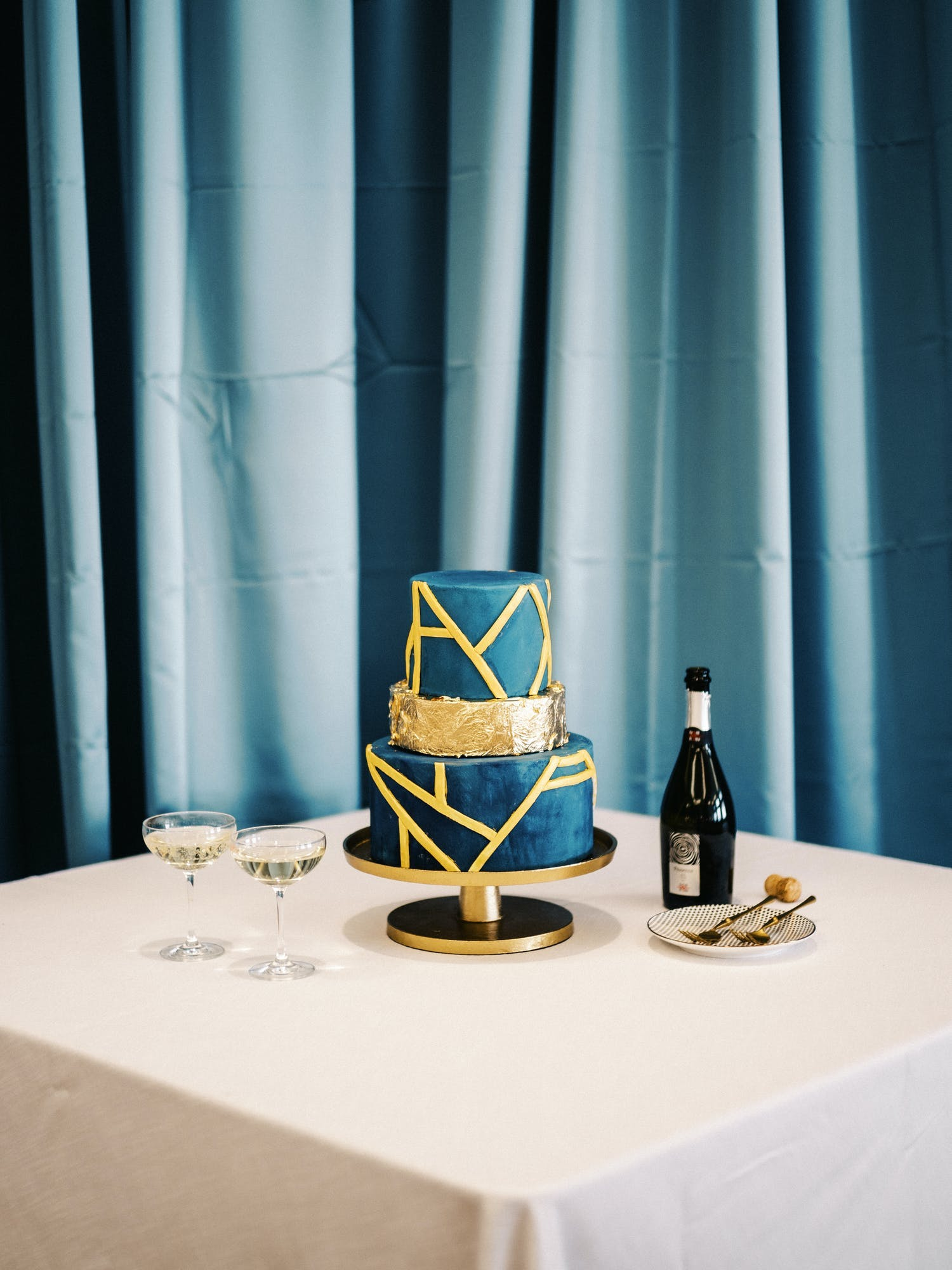 Three-tier blue and gold wedding cake with asymmetrical faceted shapes | PartySlate