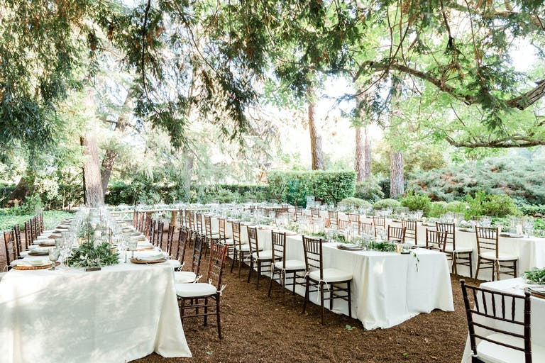 Wedding reception area in shaded winery garden with long white tables and wooden chairs at Beringer Winery   PartySlate
