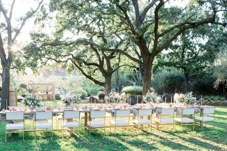White table and chairs with vibrant floral centerpieces in Chandon winery's garden wedding venue   PartySlate
