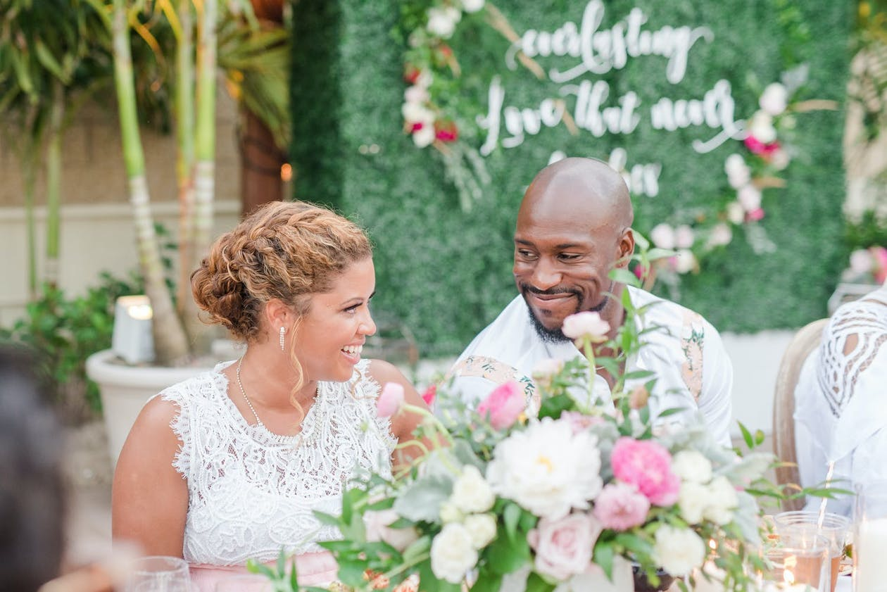 Couple look lovingly at each other during engagement party with boxwood backdrop | PartySlate