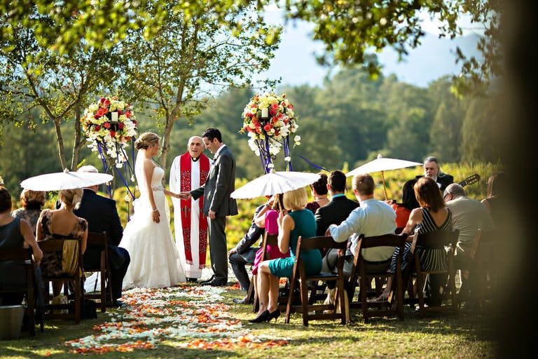 Couple exchanging vows at Sonoma winery ceremony decorated with bright floral arrangements and white umbrellas   PartySlate