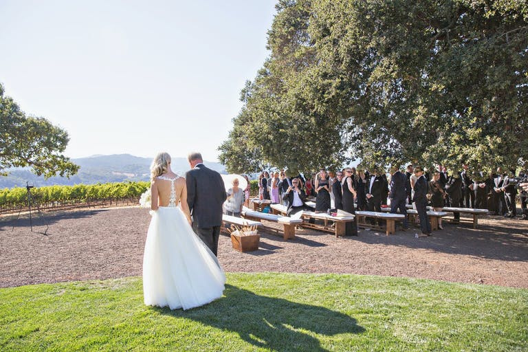 Bride given away at outdoor vineyard wedding as guests admire at Kunde Family Winery in Kenwood, CA   PartySlate
