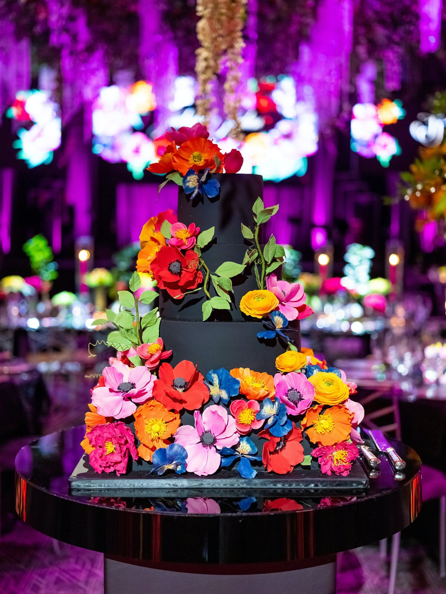 Black three-tiered cake covered in bright, colorful flowers | PartySlate | PartySlate