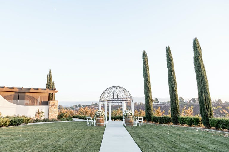 Perfectly manicured lawn with white aisle and dome altar at Avensole Winery in Temecula, CA   PartySlate
